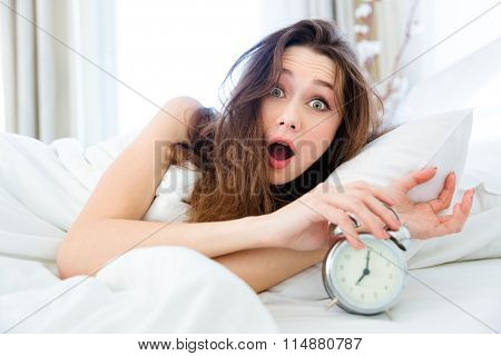 Shocked young woman waking up with alarm