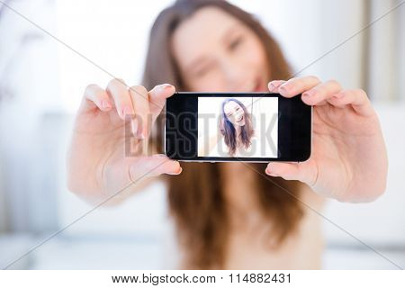 Playful positive pretty young woman winking and taking selfie with smartphone at home