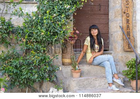 Girl Sitting In Old Town
