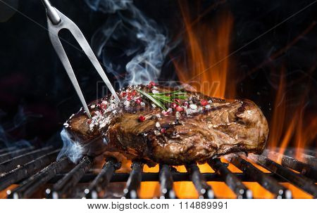 Grilled beef steak on the grill, close-up.