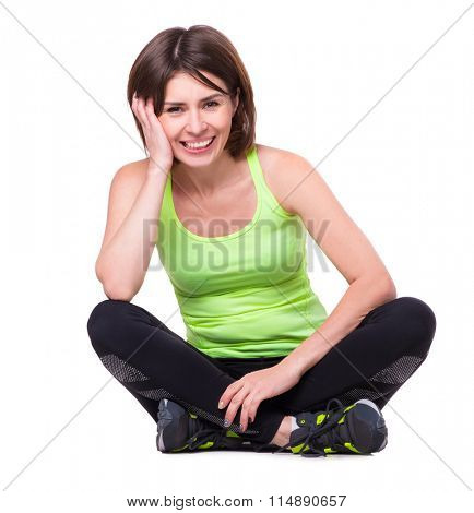 sport girl sitting on the floor with her legs crossed and resting