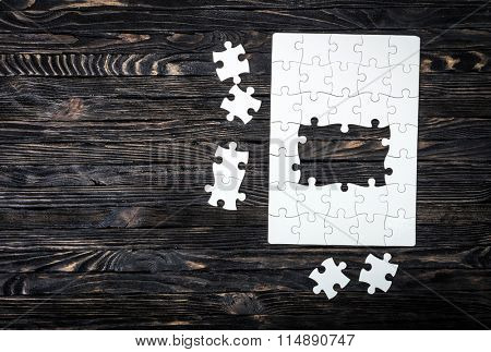 started puzzle with uncompleted center and pieces on dark wooden background