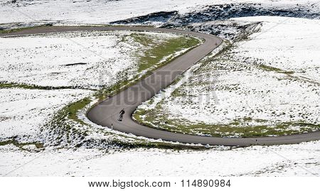 Cyclist goes downhill along a mountain road in a snowy landscape: Dolomites are a biker paradise. Passo Giau, Cortina d'Ampezzo, Dolomites, Italy.