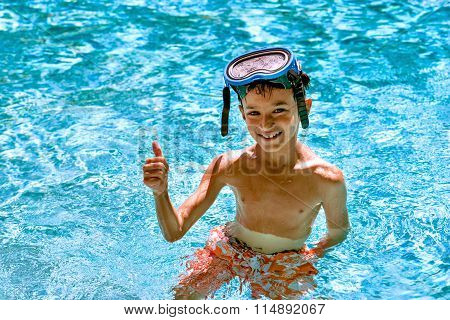 Boy eight years old inside swimming pool portrait happy fun bright day diving goggles thum