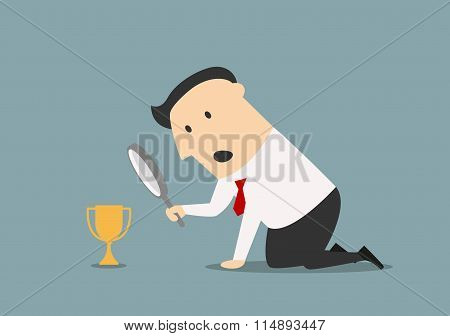 Businessman looking at trophy through magnifier