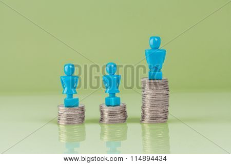 Male And Female Figurines Standing On Top Of Coins