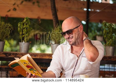 Young Man Reading A Book Has A Laugh