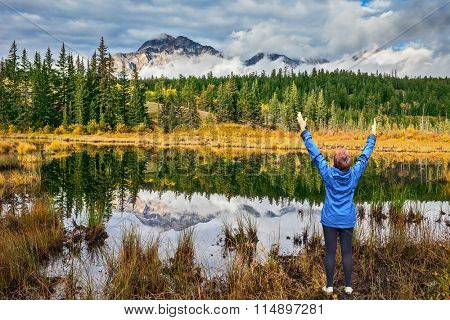 The lake reflects multi-colored autumn woods and mountains. An elderly woman in awe of the beautiful nature on the shore of the lake