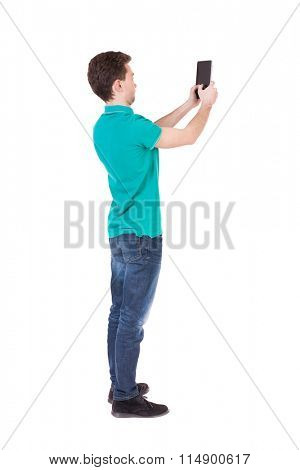 Back view of man with tablet. Standing young guy. Rear view people collection.  backside view of person.  Isolated over white background. Curly guy focused photographs.