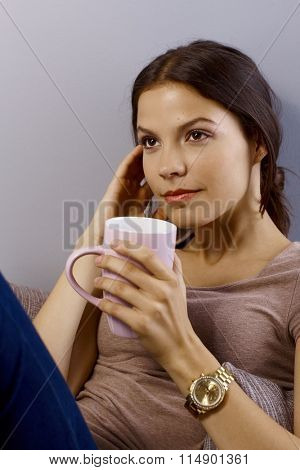Closeup portrait of young daydreaming woman drinking tea, looking away.