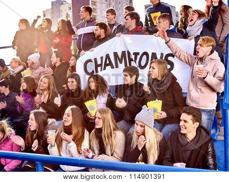 Sport fans holding banner with writting champion and singing on tribunes. Group people.