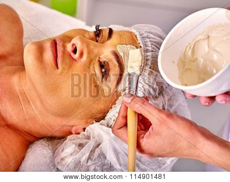 Woman middle-aged take facial and neck clay anti-aging mask in spa salon.