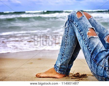 Summer girl sea.  Barefood woman sitting on coast near ocean with waves. Hot dog leg selfie.