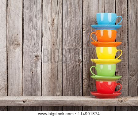 Colorful coffee cups on shelf against rustic wooden wall with copy space