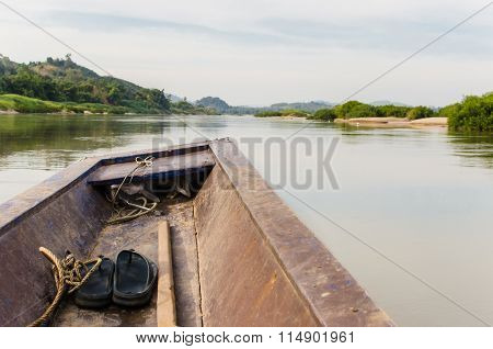 Wooden longtail boat heads out into the River