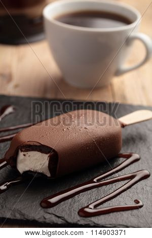 Ice cream bar coated with chocolate on a slate board and a cup of coffee