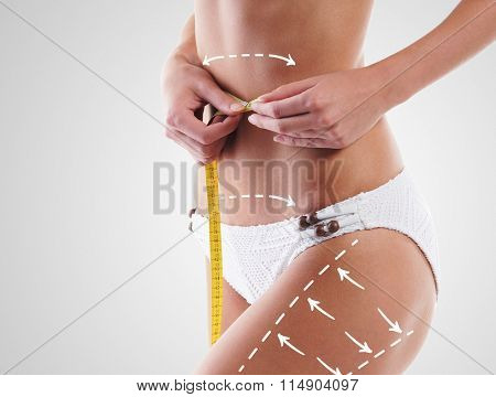 Thin woman measuring her torso with scale having arrows on hips. Plastic surgery concept.