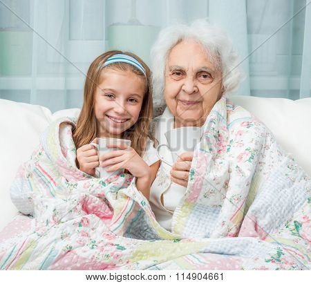 grandmother and granddaughter drink tea covered with blanket