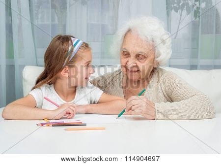 portrait of little girl with grandmother drawing with pencils