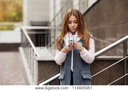 Young fashion woman calling on cell phone on city street