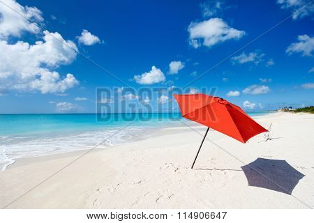 Idyllic tropical beach with red umbrella, white sand, turquoise ocean water and blue sky at deserted island in Caribbean