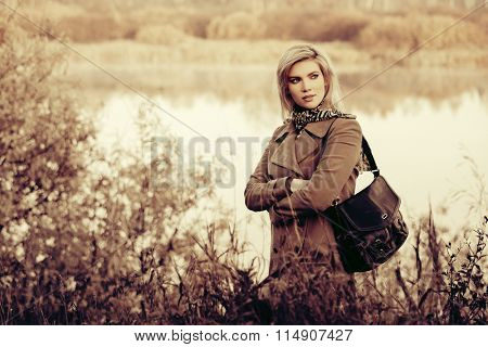 Blond fashion woman walking outdoor against an autumn nature landscape