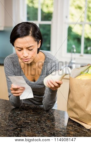 Frowning brunette holding receipt and milk in the kitchen