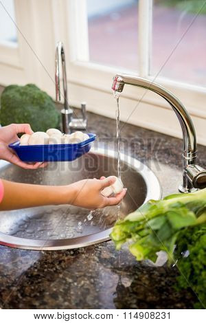 Mid section of woman washing mushrooms in the kitchen