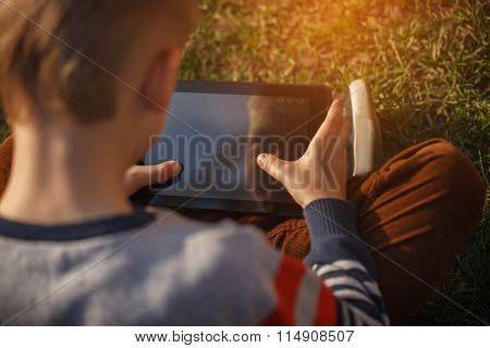Close-up Of Kid's Hands Close Up Holding  Digital Tablet For Pla