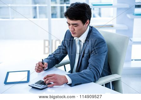 Concentrated asian businessman is working in his office