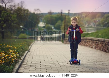 Little  Boy Riding And His Scooter Bicycle In Summer, Outdoors