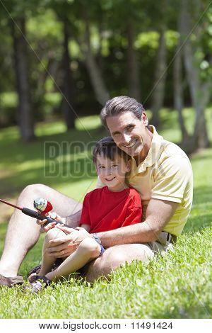Vater mit seinem Sohn an einem Fluss Fischen