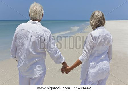 Senior Couple Holding Hands & Looking To Sea On Beach