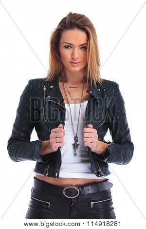 portrait of young attractive woman fixing her leather jacket while posing in studio background and looking at the camera