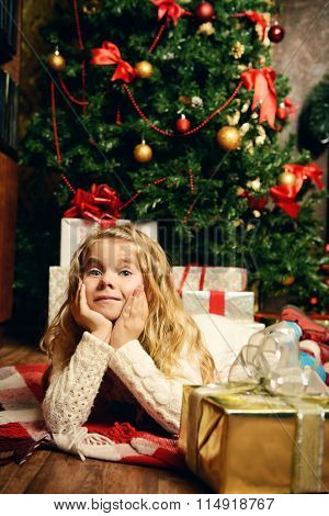 Happy little girl in Santa's hat lien in a room decorated for Christmas.