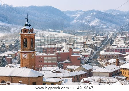 View of belfry and small town of Corneliano d'Alba covered with snow in Piedmont, Northern Italy.