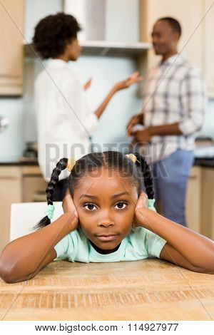 Sad girl against parents arguing in the kitchen