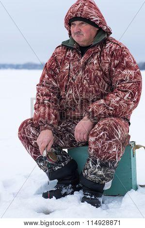 man resting on winter fishing