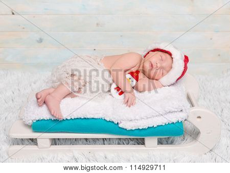 sweet newborn baby on sledge-cot with decorations