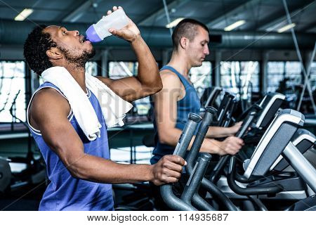 Man drinking water while using elliptical machine at gym