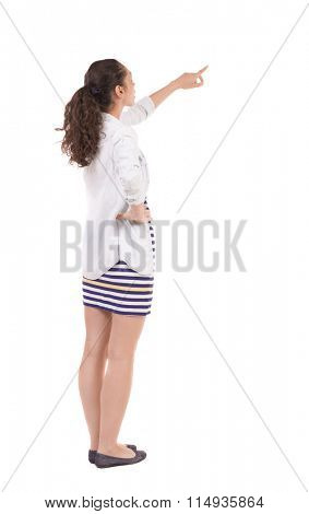 Back view of  pointing woman. beautiful girl. Rear view people collection.  backside view of person.  Isolated over white background.Girl in a striped skirt points finger up.