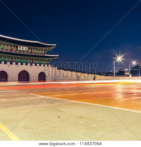 Night Shot Of Gwanghwamun Gate Of Gyeongbokgung Palace In Seoul, South Korea With Taillights And Hea