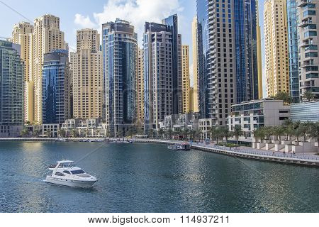 landscape background motor yacht passes through Dubai Marina on the background of skyscrapers