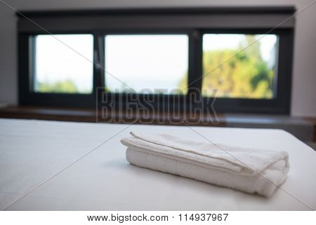 Clean white towel on the bed in hotel room