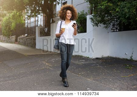 African American Woman Walking And Looking At Cellphone