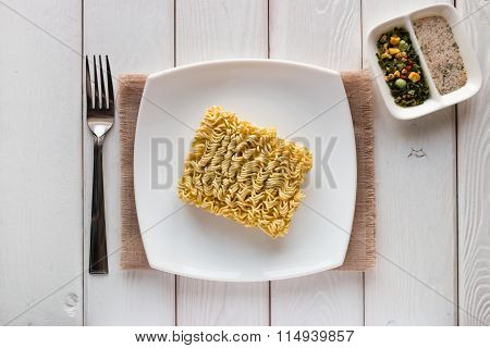 Raw Instant Noodles On A White Plate With Spices
