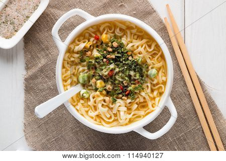 Instant Noodles In A White Plate With Vegetables And Chopsticks