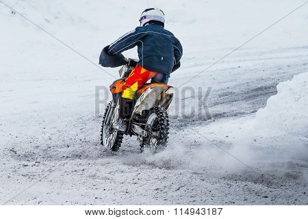racer motorcycle rides on snow-covered road