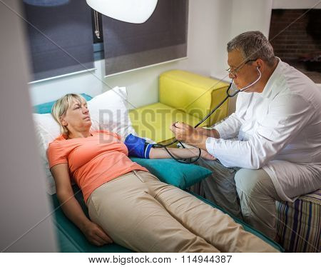 Doctor measuring blood pressure of woman at home