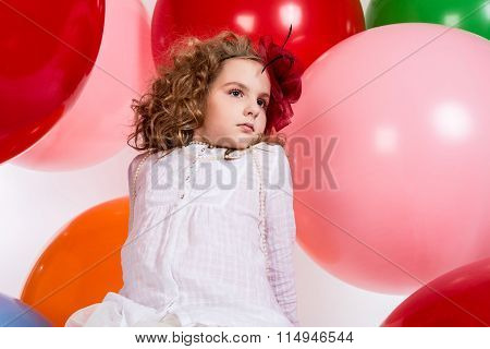 Portrait Of Teen Girl In A Hat And White Dress On A Background Of Big Colored Rubber Air Balls.